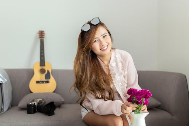Mujer asiática feliz que adorna la sala de estar con las flores hermosas en casa. Foto Premium