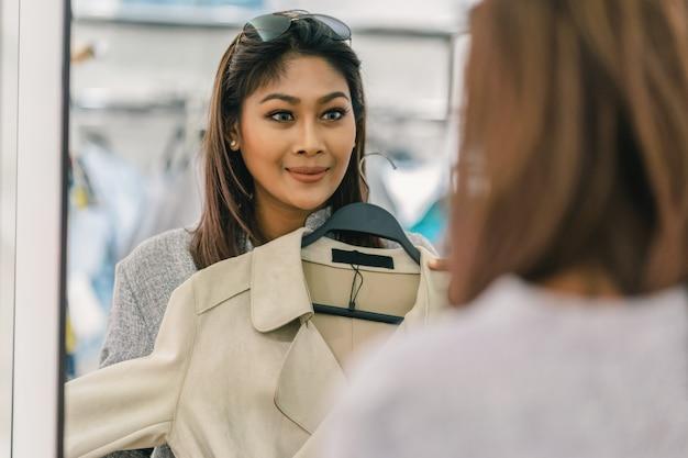 Mujer asiática feliz que elige la ropa con la reflexión del vidrio en tienda de la tienda en el departamento ce Foto Premium