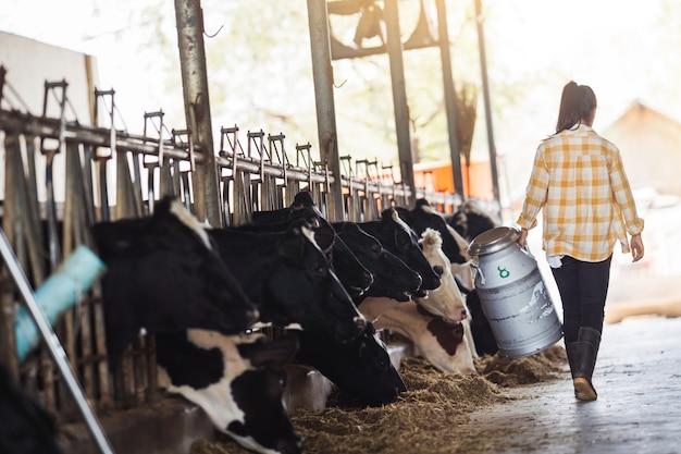 La mujer asiática del granjero está sosteniendo un recipiente de leche en su granja. Foto gratis