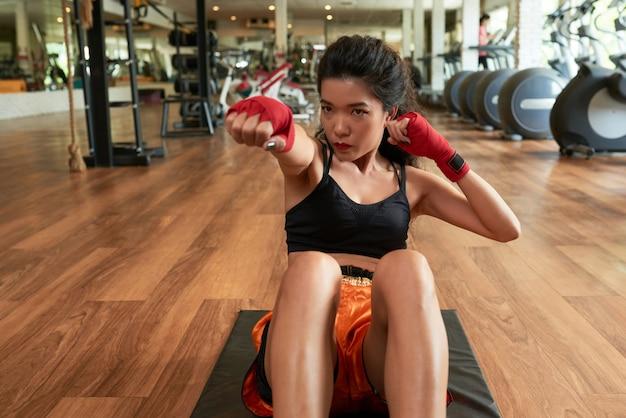 Mujer asiática haciendo ejercicios con sus brazos envueltos con banda roja Foto gratis