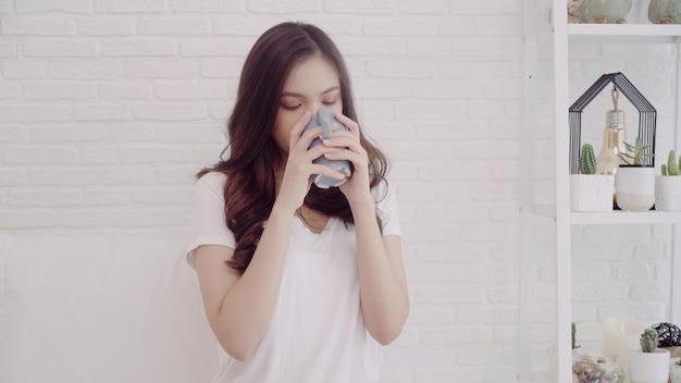 Mujer asiática hermosa feliz que sonríe y que bebe una taza de café o de té en cama Foto gratis