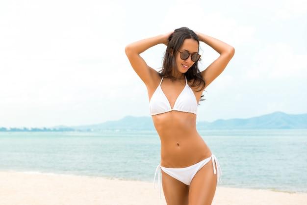 Mujer asiática hermosa joven en biniki blanco en la playa en verano Foto Premium