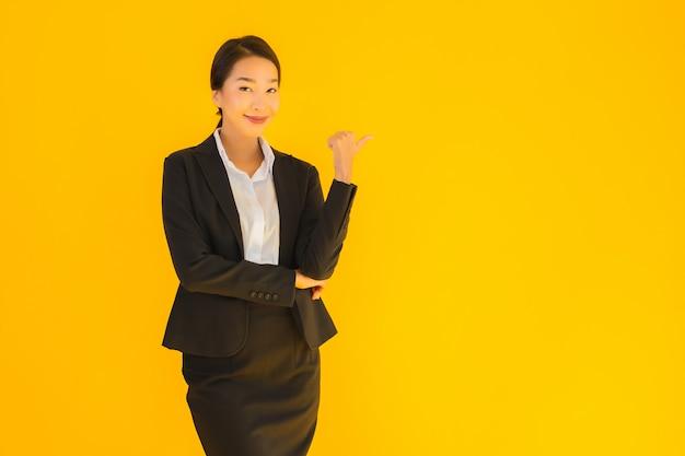 Mujer asiática hermosa joven de negocios con una sonrisa feliz apuntando hacia el lado Foto gratis