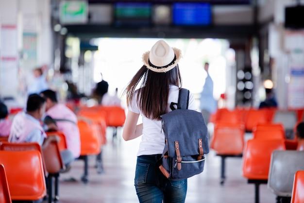 Mujer asiática hermosa que sonríe con el mapa y el bolso en la estación de autobuses Foto gratis