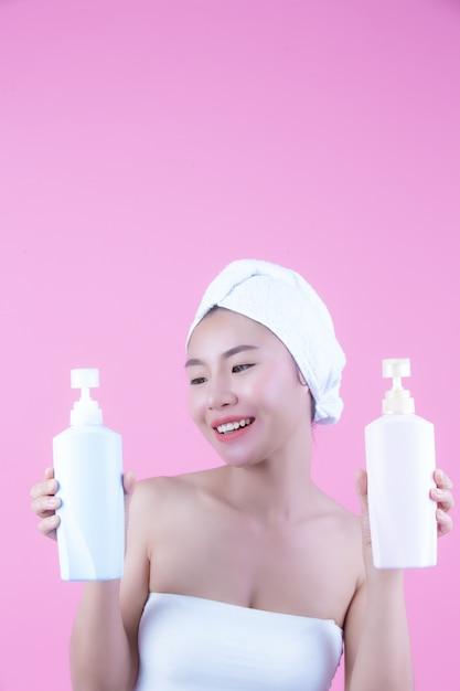 Mujer asiática hermosa que sostiene una botella de producto en un fondo rosado. Foto gratis