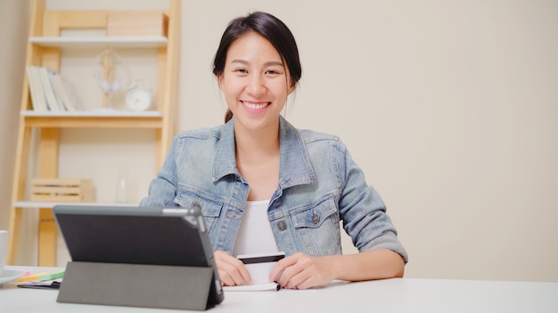 Mujer asiática hermosa que usa la tableta que compra compras en línea por la tarjeta de crédito mientras que lleve la sentada casual en el escritorio en sala de estar en casa. Foto gratis