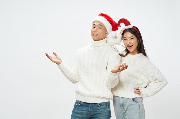 Mujer asiática y hombre con sombreros de santa Foto Premium