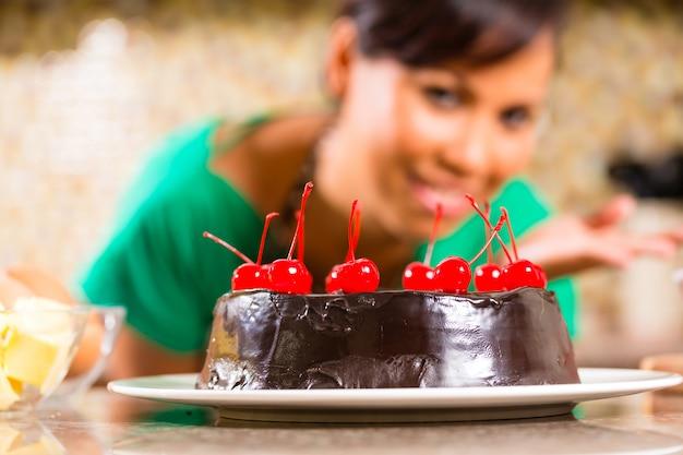 Mujer asiática hornear pastel de chocolate en la cocina Foto Premium