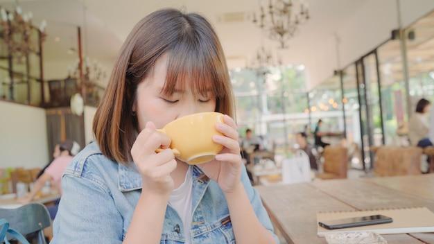 Mujer asiática independiente del negocio que bebe la taza caliente de té verde o de café mientras que se sienta en la tabla en café. Foto gratis