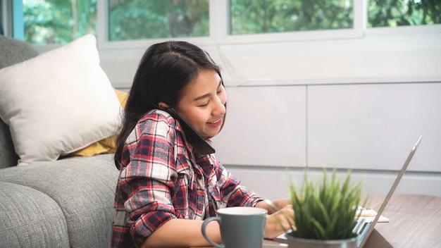 Mujer asiática independiente que trabaja en casa, mujer de negocios que trabaja en la computadora portátil y que usa el teléfono móvil que habla con el cliente en el sofá en la sala de estar en casa. Foto gratis