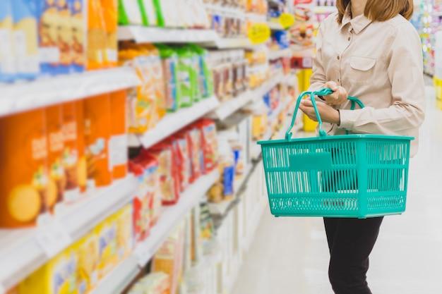 Mujer asiática joven con la cesta en el supermercado. compras, consumismo y concepto de personas. Foto Premium