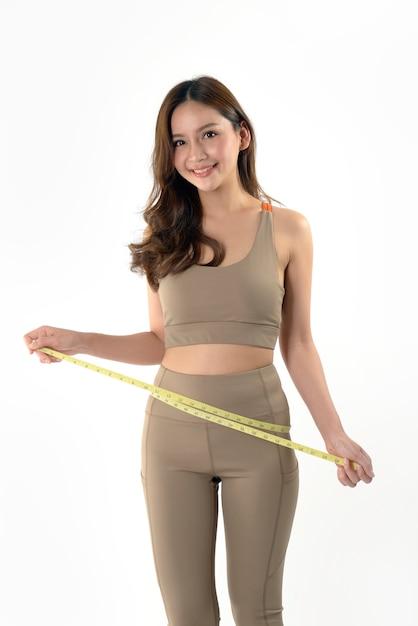 Mujer asiática joven delgada que mide de su cuerpo Foto Premium