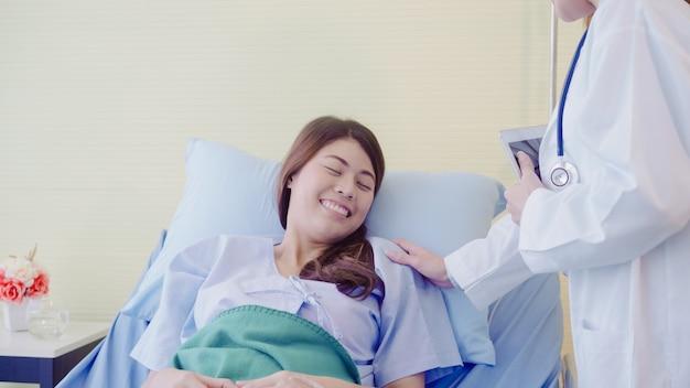Mujer asiática joven del doctor que habla y que lleva a cabo la mano para las mujeres pacientes en cama enferma. Foto gratis
