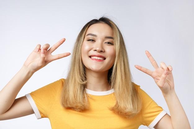 Mujer asiática joven feliz que muestra dos dedos o gesto de la victoria Foto Premium