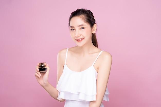 Mujer asiática joven hermosa con la piel blanca fresca limpia que sostiene el producto de la crema del tratamiento facial una mano con sonrisa. Foto Premium