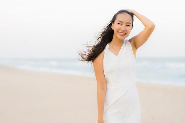 Mujer asiática joven hermosa del retrato feliz y sonrisa en el mar y el océano de la playa Foto gratis