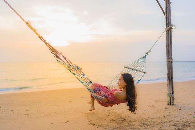 Mujer asiática joven hermosa del retrato que se sienta en la hamaca con el mar y el oce cercano felices de la playa de la sonrisa Foto gratis