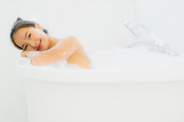 La mujer asiática joven hermosa del retrato toma una bañera en cuarto de baño Foto gratis