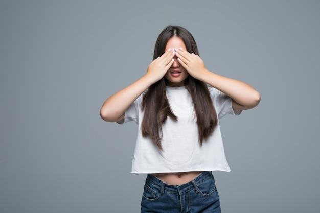 La mujer asiática joven oculta su cara, foto del estudio en fondo gris. concepto de problema de fobia social. chica cubre la cara con las manos sintiendo miedo emoción. Foto gratis