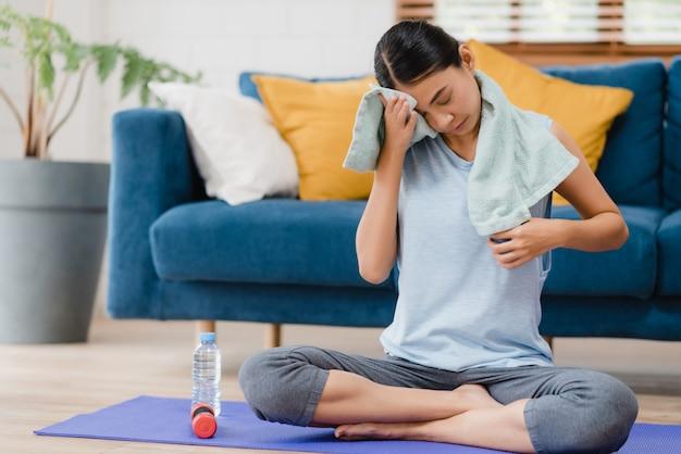 Mujer asiática joven que bebe agua porque siente descanso agotado después de hacer ejercicio en la sala de estar Foto gratis