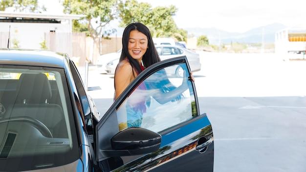 Mujer asiática joven que sale del coche en la gasolinera Foto gratis