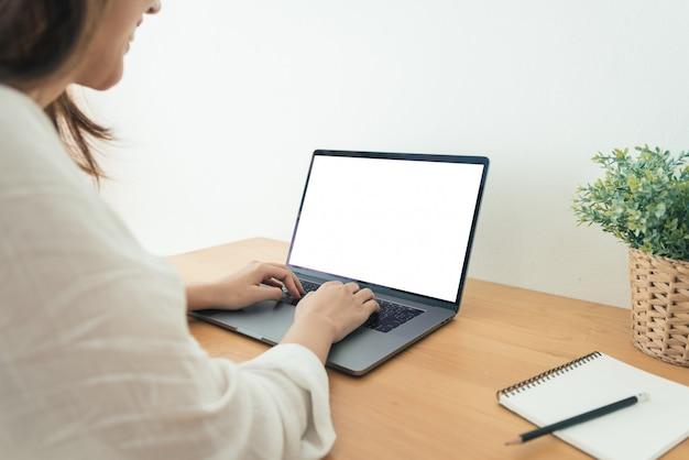 Mujer asiática joven que trabaja usando y escribiendo en la computadora portátil con mock up pantalla en blanco en blanco Foto gratis
