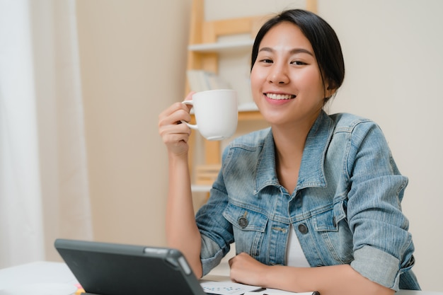 Mujer asiática joven que trabaja usando la tableta que comprueba medios sociales y que bebe el café mientras que relájese en el escritorio en sala de estar en casa. Foto gratis