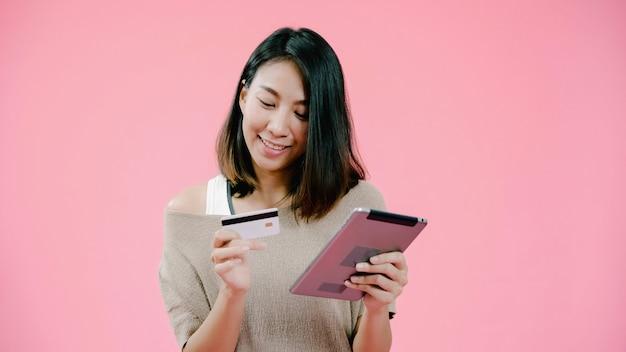 Mujer asiática joven que usa la tableta que compra compras en línea por la tarjeta de crédito que siente la sonrisa feliz en ropa informal sobre tiro rosado del estudio del fondo. la mujer alegre adorable sonriente feliz disfruta de éxito Foto gratis