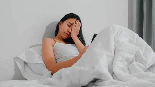 Mujer asiática joven que usa el teléfono inteligente que comprueba los medios sociales que se siente feliz sonriendo mientras está acostado en la cama después de despertarse por la mañana, bella dama hispana atractiva sonriendo relajarse en el dormitorio en casa. Foto gratis