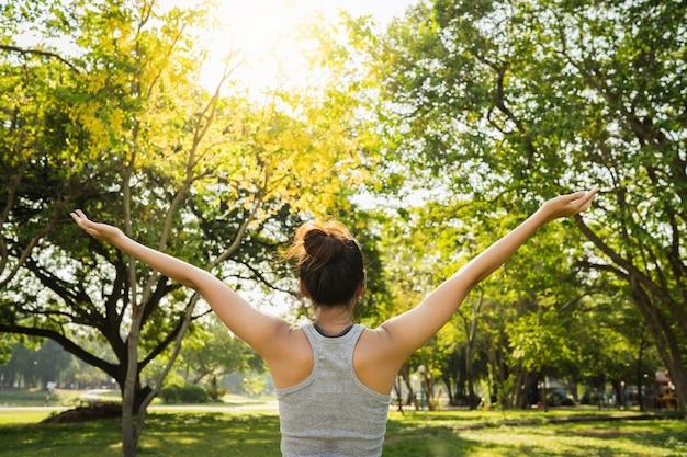 La mujer asiática joven sana del corredor calienta el cuerpo que estira antes de ejercicio Foto gratis