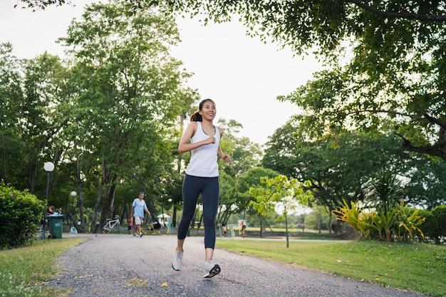 Mujer asiática joven sana del corredor en la ropa de los deportes que corre y que activa en la acera Foto gratis