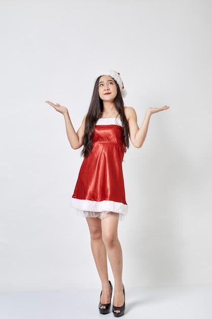 Mujer asiática joven en el sombrero de santa en blanco Foto Premium