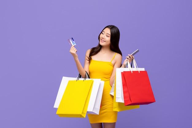Mujer asiática llevando bolsas de compras con tarjeta de crédito y teléfono inteligente en manos Foto Premium