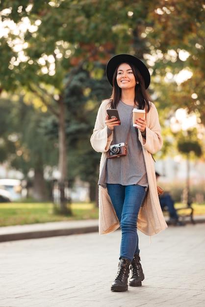 Mujer asiática moderna que sostiene el teléfono móvil y la taza de café mientras camina en el parque al aire libre Foto gratis