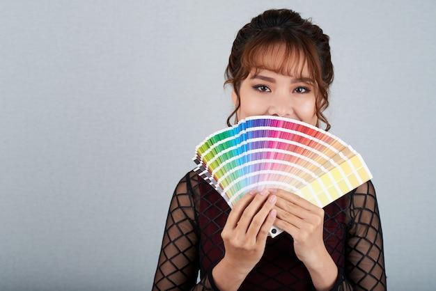 Mujer asiática mostrando paleta de colores cubriendo su boca con ella Foto gratis
