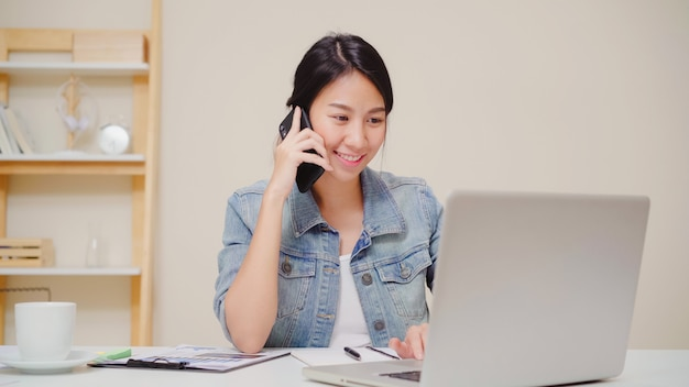 Mujer asiática del negocio elegante hermoso en la ropa de sport elegante que trabaja en el ordenador portátil y que habla en el teléfono mientras que se sienta en la tabla en oficina creativa. Foto gratis