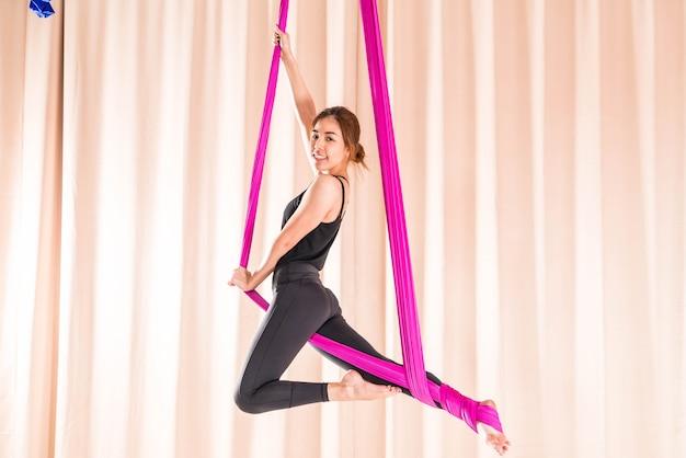 Mujer asiática que entrena en sala de fitness con elementos de yoga mosca Foto Premium
