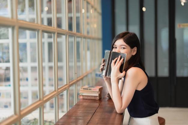 Mujer asiática que lee un libro en el coffeeshop. Foto Premium