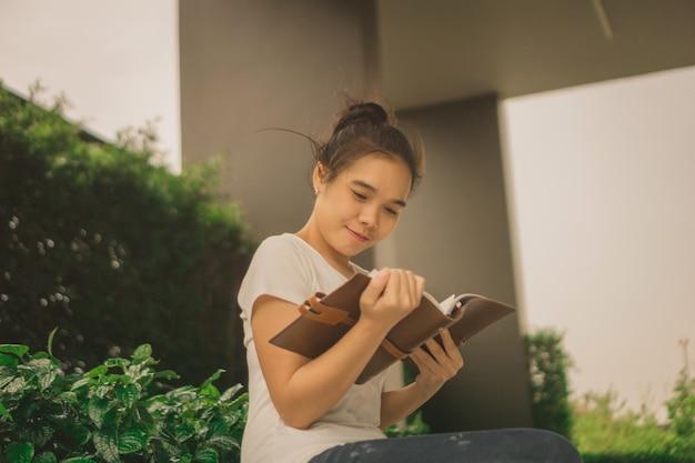 Mujer asiática que lee un libro en parque con los rascacielos en el fondo Foto Premium
