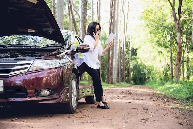 Mujer asiática que llama al reparador o al personal de seguros para arreglar un problema del motor del automóvil en una carretera local Foto gratis