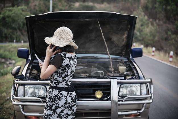 Mujer asiática que llama a un técnico de reparaciones o de seguros para solucionar un problema de motor de automóvil en una carretera local Foto gratis