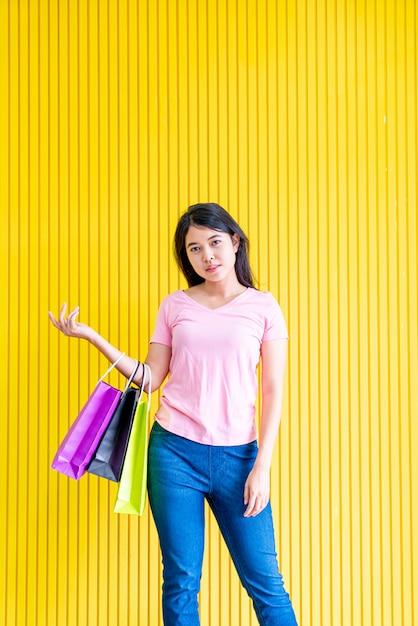 Mujer asiática que sostiene bolsos de compras Foto Premium