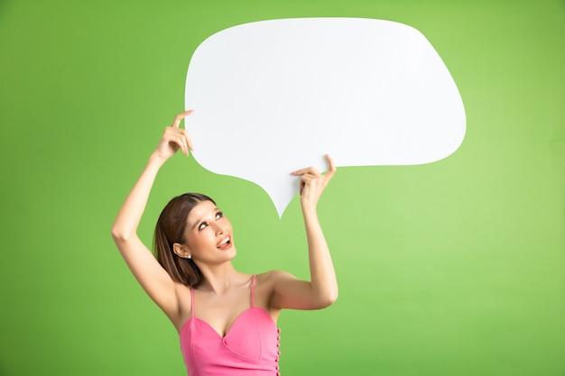 Mujer asiática que sostiene y que mira para arriba a la burbuja del discurso con el espacio vacío para el texto en verde Foto gratis