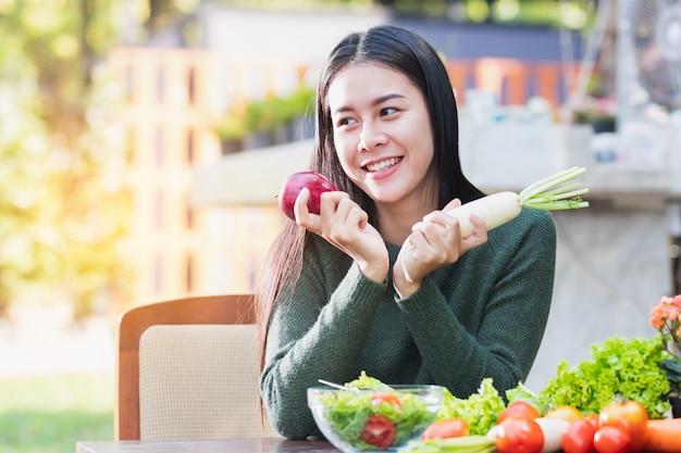 Mujer asiática que sostiene las verduras y la fruta que presentan con feliz. Foto Premium
