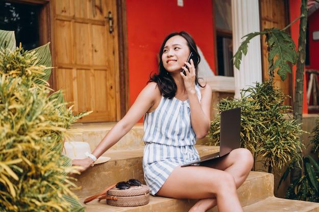Mujer asiática que trabaja en la computadora portátil en vacaciones y sentado en las escaleras Foto gratis