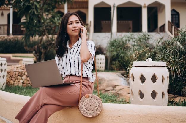 Mujer asiática que trabaja en la computadora portátil en vacaciones Foto gratis