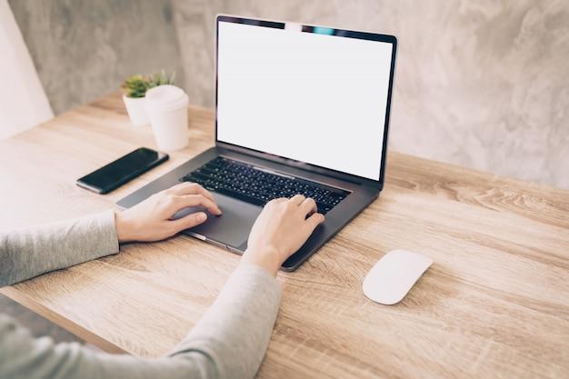 Mujer asiática que usa la computadora portátil para trabajar en la mesa de madera Foto Premium