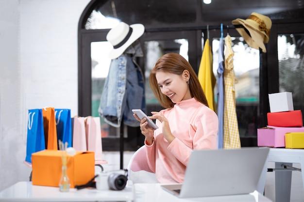 Mujer asiática que usa un teléfono inteligente y sonriendo mientras está sentado en el taller Foto Premium