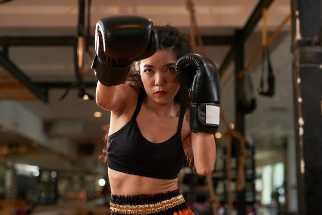 Mujer asiática recortada entrenando en guantes de boxeo en la práctica de muay thai Foto gratis