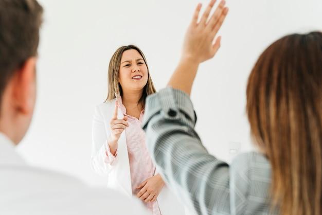 Mujer asiática respondiendo preguntas de compañeros de trabajo Foto gratis